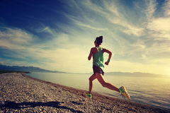 coureur de femme de forme physique fonctionnant sur la traînée de bord de la mer de lever de soleil images stock