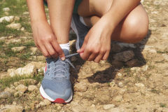 Coureur de femme restant au sol et attachant des dentelles sur le sport Image stock