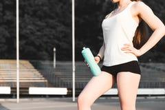 Coureur de jeune femme réchauffant avant course sur la ville un repos de fille après le jeu des sports photographie stock libre de droits