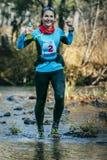 Coureur de jeune femme souriant tout en traversant une rivière de montagne Images stock
