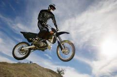 Coureur de motocross dans l'entre le ciel et la terre contre le ciel nuageux photos stock
