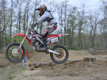 Coureur de motocross sautant par-dessus une petite côte Image stock