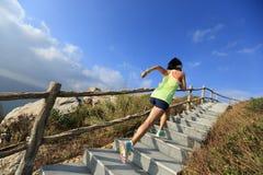 Coureur de traînée de femme fonctionnant sur des escaliers de montagne Image libre de droits