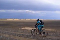 Coureur de vélo dans le désert de tempête Photographie stock