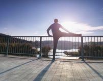 Coureur faisant étirant l'exercice sur le pont Un homme raide actif photographie stock