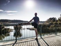 Coureur faisant étirant l'exercice sur le pont Un homme raide actif photos stock