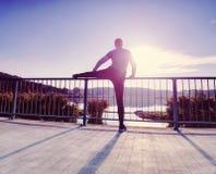 Coureur faisant étirant l'exercice sur le pont Un homme raide actif images libres de droits