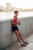 Coureur femelle avec de l'eau l'eau en bouteille fatiguée Images stock