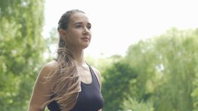 Coureur femelle avec de longues courses de cheveux en parc dehors, beau pulser de dame lent banque de vidéos