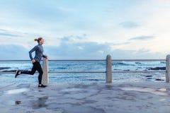 Coureur femelle fonctionnant sur la promenade de bord de la mer Photos stock
