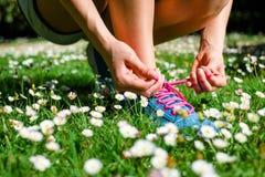 Coureur femelle laçant les chaussures de course au printemps Photo libre de droits