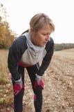 Coureur femelle mûr faisant une pause pour le souffle pendant l'exercice en bois image stock