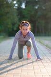 Coureur femelle prêt pour le sprint fonctionnant Femme à la ligne de départ i Image stock