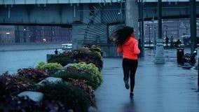 Coureur femelle sportif de jeune métis fonctionnant le long du remblai de parc de ville le soir, tir de mouvement lent clips vidéos