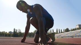 Coureur hispanique en position de départ à courir sur la voie, accomplissement de but dans le sport photo libre de droits