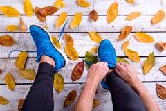 Coureur méconnaissable dans des chaussures de sports attachant des dentelles Automne le Photo stock