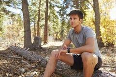Coureur masculin avec le smartwatch se reposant dans la forêt, regardant loin Photos stock