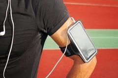 Coureur masculin avec le téléphone intelligent mobile, écoutant la musique pendant la séance d'entraînement Courant, pulser, card Photos stock