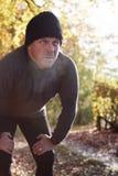 Coureur masculin mûr faisant une pause pour le souffle pendant l'exercice en bois image stock