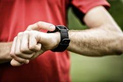 Coureur regardant la montre de sport photos stock