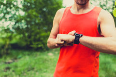 Coureur regardant le smartwatch de montre de sport images libres de droits