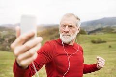 Coureur supérieur actif en nature prenant le selfie avec le téléphone intelligent Photographie stock
