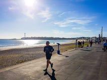 Coureur sur la plage de Weymouth photo stock