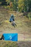Coureur sur les sauts faisants du vélo de montagne d'un tremplin Images stock