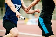 Coureurs d'athlètes d'hommes de course de relais photos libres de droits