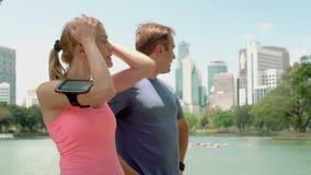 Coureurs d'homme et de femme pulsant en parc Formation courante de forme physique masculine femelle convenable de sport avoir le  banque de vidéos