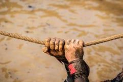 Coureurs de course de boue, défaisant des obstacles à l'aide des cordes E image stock