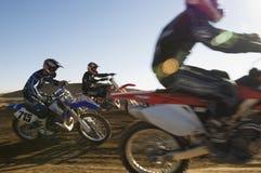 Coureurs de motocross emballant dans le désert photos libres de droits