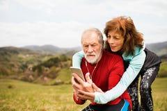 Coureurs supérieurs actifs en nature prenant la photo avec le téléphone intelligent Photo libre de droits