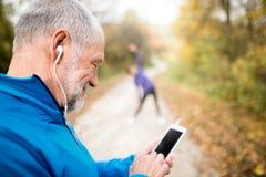 Coureurs supérieurs en nature, s'étendant Homme avec le smartphone avec e Images stock
