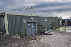 Courez en bas de l'immeuble de bureaux, fait de fer ondulé vert, avec des déchets et des débris devant le bâtiment Photographie stock libre de droits