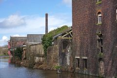 Courez en bas des bâtiments industriels à côté d'un canal Photos stock