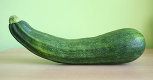 Courgette. One courgette with green background stock images