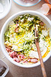 Courgette cake frittata ingredients mixed white bowl - eggs, flour, grated courgette, bacon, feta, mascarpone and cheddar. Courgette cake frittata ingredients royalty free stock photography
