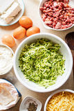 Courgette cake frittata ingredients in white bowl - eggs, flour, grated courgette, bacon, feta, mascarpone and cheddar. Courgette cake frittata ingredients in stock images