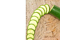 Courgette cut to slices on breadboard Stock Images