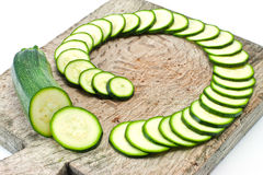 Courgette cut to slices on breadboard Royalty Free Stock Photography
