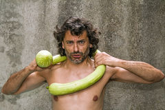 Courgette fight. Man have a funny fight with a big zucchini squash stock photography