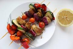 Courgette grillée sur des brochettes avec les tomates, l'oignon, les poivrons, et les champignons avec le citron d'un plat blanc  image libre de droits