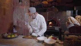 Courgette professionnelle de tranches de cuisinier se trouvant sur le panneau de cuisine dans la cuisine du restaurant Cuisson de clips vidéos