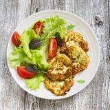 Courgettepannekoeken en verse groentesalade op witte plaat stock afbeelding