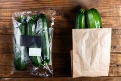 Courgettes в полиэтиленовом пакете ПРОТИВ бумажного мешка Выберите более менее пластиковую концепцию стоковые фото