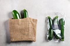 Courgettes в полиэтиленовом пакете ПРОТИВ бумажного мешка Выберите более менее пластиковую концепцию стоковая фотография rf