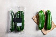 Courgettes в полиэтиленовом пакете ПРОТИВ бумажного мешка Выберите более менее пластиковую концепцию стоковое фото