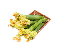 Courgettes  with flowers in brown basket isolated. Bunch of fresh raw courgettes  with flowers in brown basket isolated on white background Royalty Free Stock Photo
