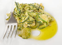Courgettes with fork on white dish. Royalty Free Stock Image